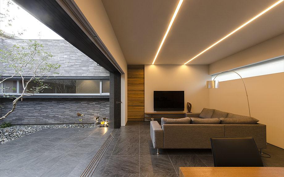 大阪府高槻市に建てられたコートハウス,中庭のある家,照明の点いたリビング