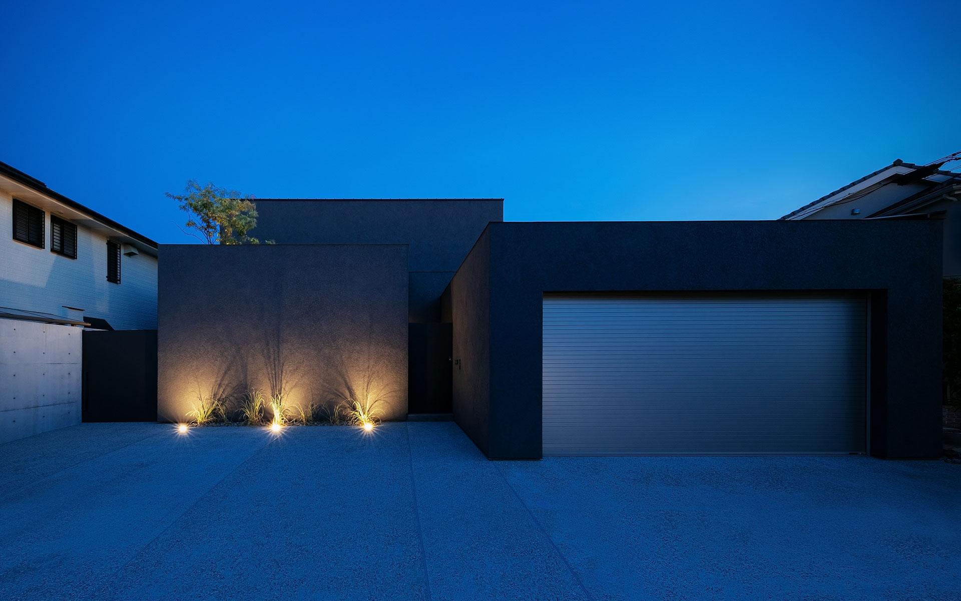 水盤のあるコートハウスのライトアップされた夕景写真